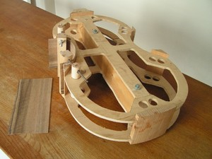 The mould with corner and top and bottom blocks attached and the first rib bent and cramped to shape. The piece of wood to the left is the second rib before bending.